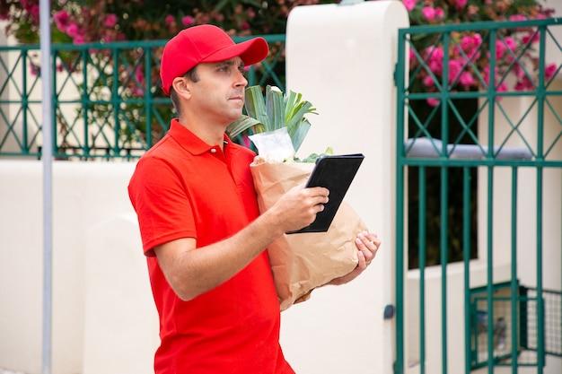 Fattorino accigliato portando un sacchetto di carta dal negozio di alimentari. corriere di mezza età in camicia rossa che cerca indirizzo tramite tablet e consegna l'ordine. servizio di consegna di cibo e concetto di acquisto online