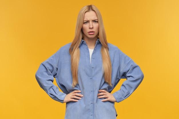 眉をひそめている女の子、金髪の長い髪の不満そうな女性。青いシャツを着ています。人と感情の概念。腰に手を置きます。オレンジ色の背景の上に分離されたカメラで見て