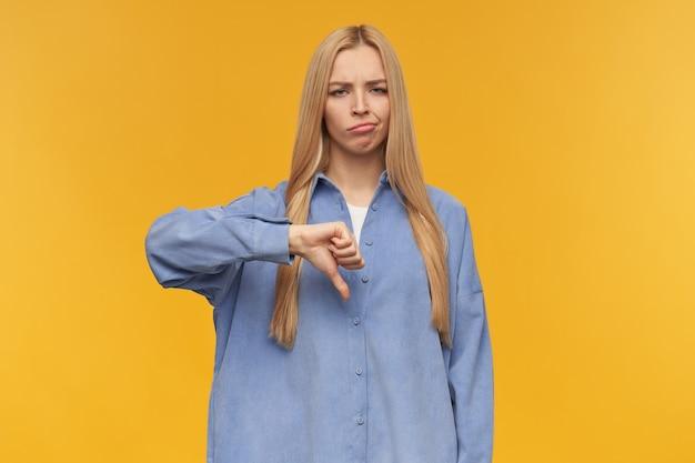찡그림 소녀, 금발의 긴 머리를 가진 불만 보는 여자. 파란색 셔츠를 입고. 사람과 감정 개념. 아래로 엄지 손가락 표시, 비 승인. 오렌지 배경 위에 절연 카메라를보고