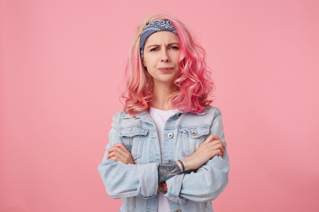 Frowning lady with pink hair and tattooed hand, looking with disapproval and discontent, standing with crossed arms, wearing a white t-shirt and denim jacket.
