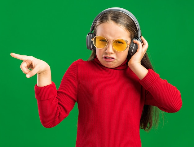 Frowning little blonde girl wearing headphones and sunglasses pointing at side and grabbing headphones  isolated on green wall
