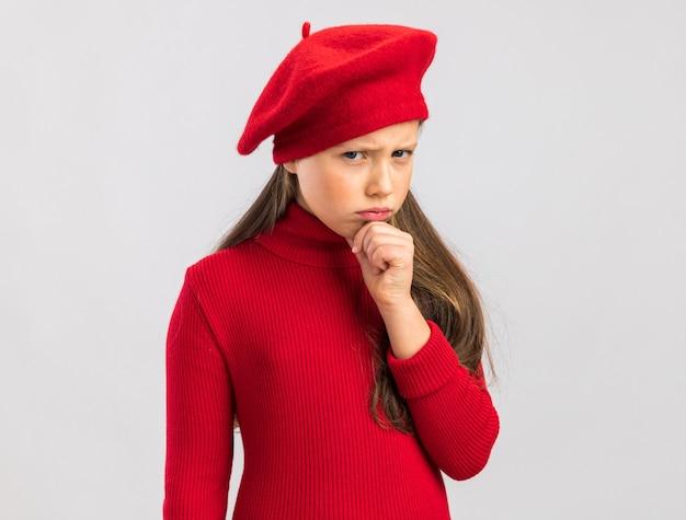 Piccola ragazza bionda accigliata che indossa un berretto rosso che tiene la mano sul mento isolato sul muro bianco con spazio per le copie