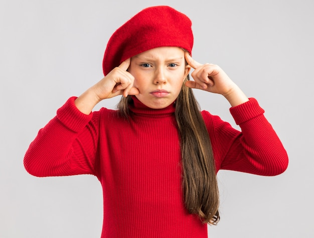 Frowning little blonde girl wearing red beret looking at camera doing think gesture isolated on white wall