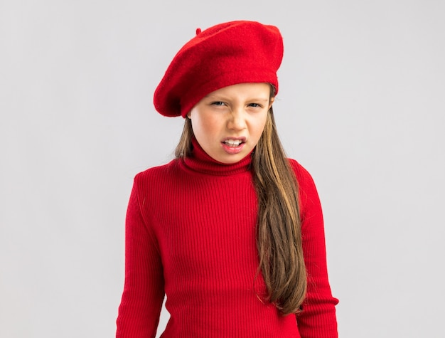 Frowning little blonde girl wearing red beret looking at camera isolated on white wall with copy space Premium Photo