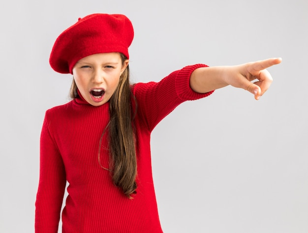 Frowning little blonde girl wearing red beret looking at camera pointing at side isolated on white wall Premium Photo