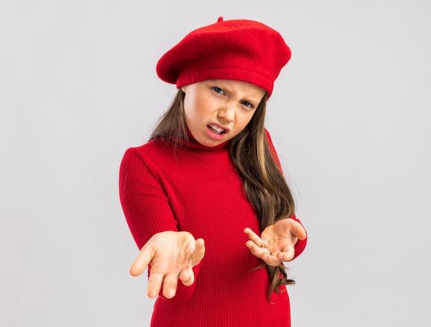 Piccola ragazza bionda accigliata che indossa un berretto rosso che guarda e indica davanti isolato sul muro bianco con spazio per le copie