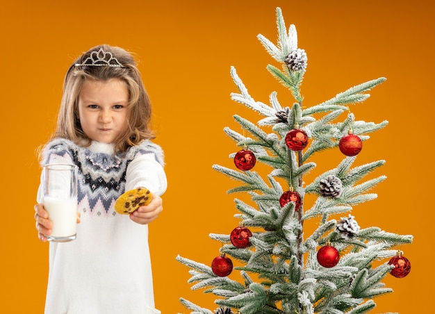 Frowning little girl standing nearby christmas tree wearing tiara with garland on neck holding out glass of milk with cookies at camera isolated on orange background