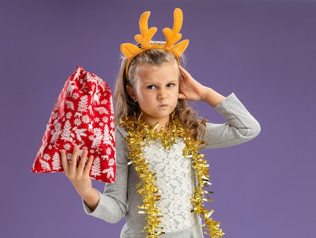 Frowning little girl wearing christmas hair hoop with garland on neck holding christmas bag putting hand on head isolated on blue background