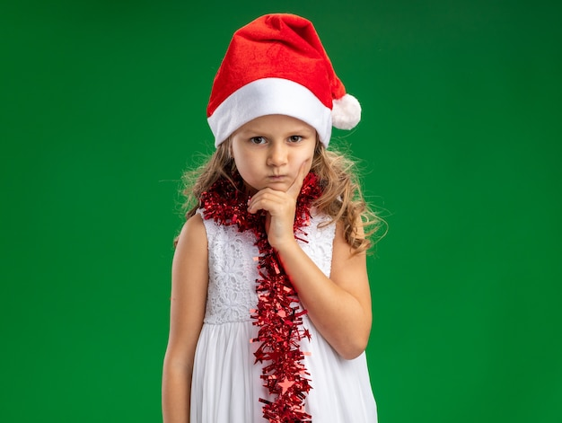 Frowning little girl wearing christmas hat with garland on neck putting hand on chin isolated on green background