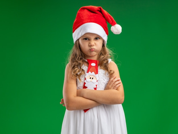 Frowning little girl wearing christmas hat with tie crossing hands isolated on green wall