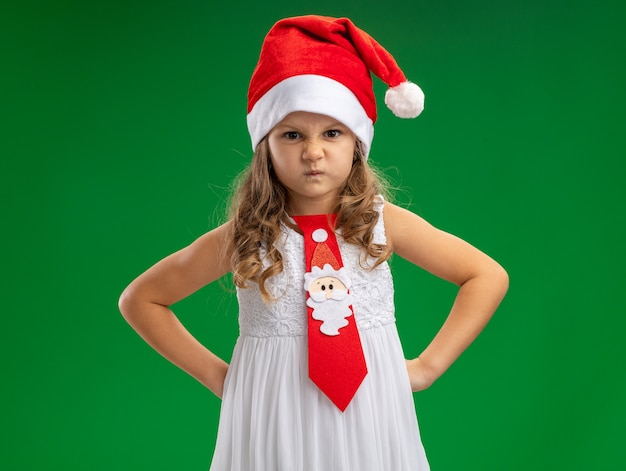 Frowning little girl wearing christmas hat with tie putting hands on hip isolated on green background