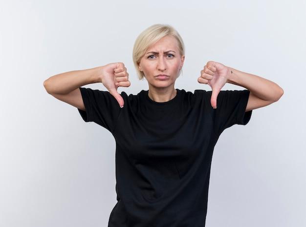 Хмурится блондинка средних лет славянская женщина смотрит в камеру, показывает палец вниз, изолированные на белом фоне