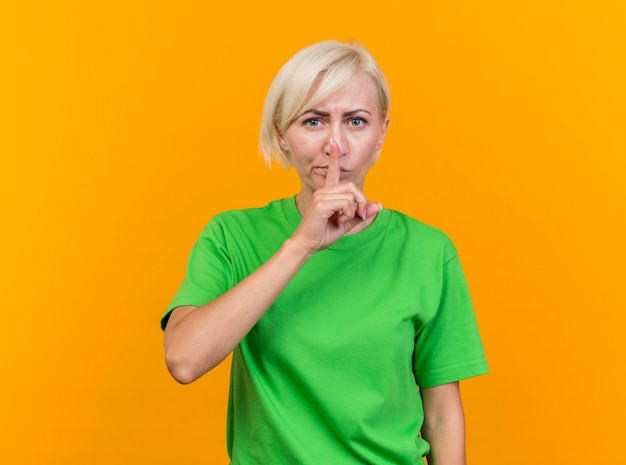 Хмурящаяся белокурая славянская женщина средних лет, смотрящая вперед, делает жест молчания изолирована на желтой стене с копией пространства