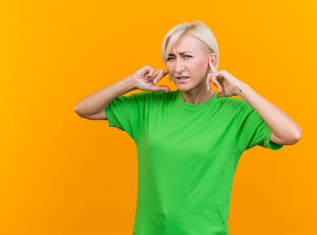 Frowning middle-aged blonde slavic woman looking at camera putting fingers on ears isolated on yellow background with copy space