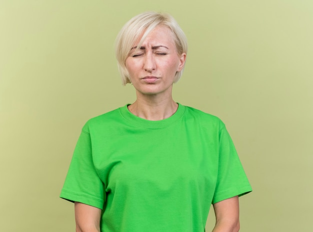 Хмурится блондинка средних лет славянская женщина, стоящая с закрытыми глазами на оливково-зеленом фоне