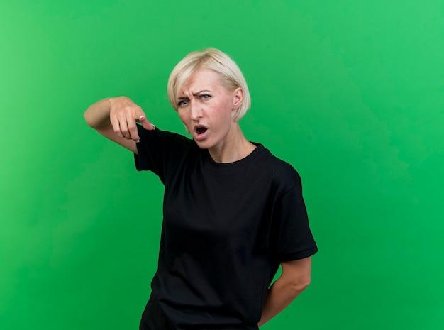 緑の壁に隔離された後ろの後ろに手を保ちながら正面を見て、指している眉をひそめている中年のブロンドの女性
