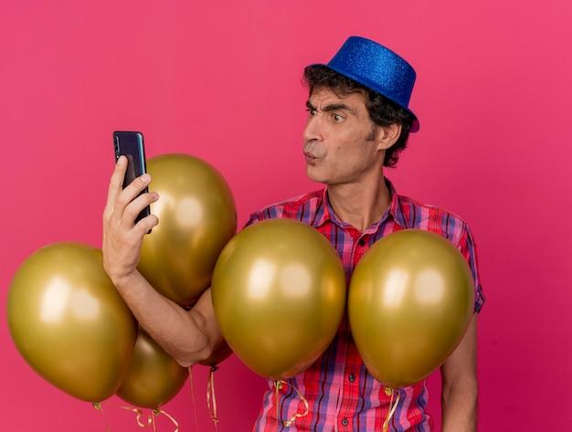 Accigliato uomo caucasico di mezza età del partito che indossa il cappello del partito in piedi dietro i palloncini che tengono e guardando il telefono cellulare isolato su sfondo cremisi