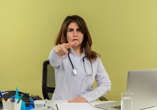 医療用ローブと聴診器を身に着けている眉をひそめている中年の女性医師が分離されたピストルジェスチャーを行う医療ツールクリップボードとラップトップで机に座っている