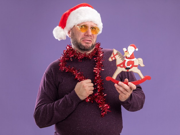 Frowning middle-aged man wearing santa hat and tinsel garland around neck with glasses holding santa on rocking horse figurine  isolated on purple wall