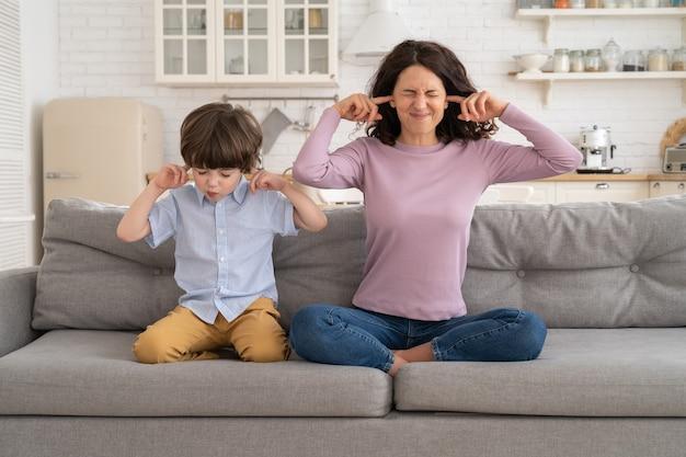 しかめっ面のママと息子は騒々しい音楽から耳を覆うソファに座っています