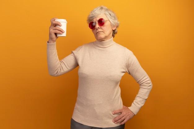 Anziana accigliata che indossa un maglione a collo alto cremoso e occhiali da sole che tengono una tazza di caffè in plastica tenendo la mano sulla vita isolata sul muro arancione
