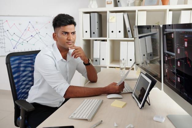 Хмурый задумчивый молодой индийский трейдер, наблюдающий за фондовым рынком, глядя на экраны, анализируя курс акций