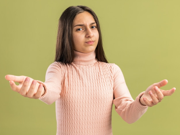 올리브 녹색 벽에 격리된 앞을 보고 가리키는 예쁜 10대 소녀 무료 사진