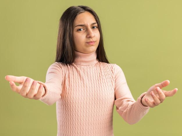Accigliata bella ragazza adolescente che guarda e indica davanti isolata sul muro verde oliva