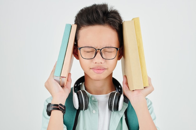 Frowning schoolboy tired of studying closing eyes and squeezing head between books
