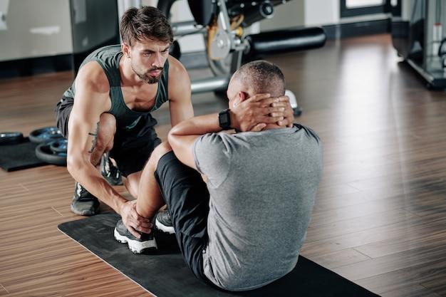 Нахмурившись, серьезный фитнес-трансер помогает мужчине делать приседания и хрустит на коврике в тренажерном зале
