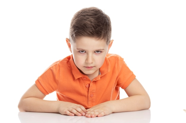 Frowning serious school-age boy in a bright orange polo t-shirt sits at a table. isolirvoan on a white background.