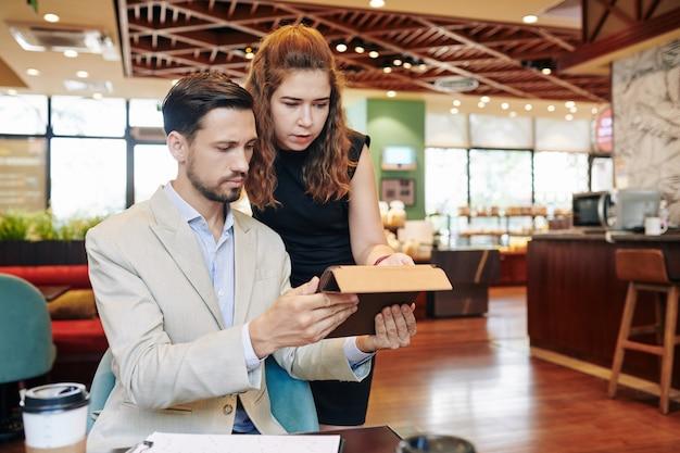 Хмурясь, серьезные молодые деловые люди читают статью на цифровом планшете во время встречи в кафе