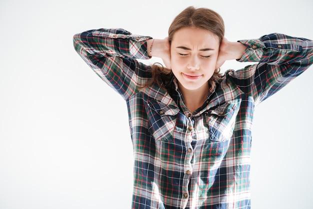 Хмурится подчеркнутая женщина в клетчатой рубашке прикрыла уши руками