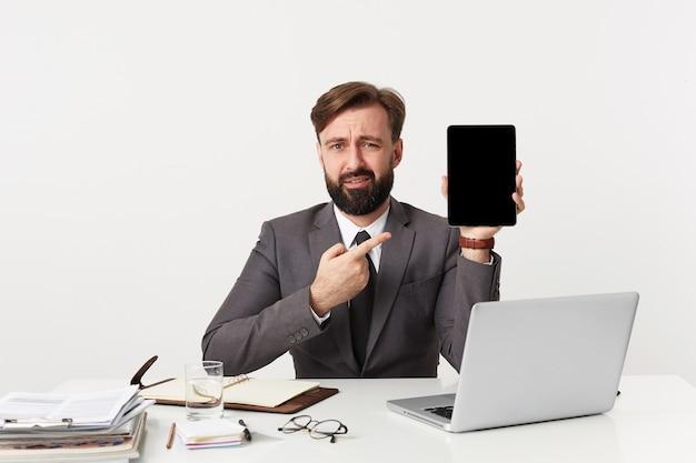 불행한 매력적인 수염 사업가, 사무실에서 바탕 화면에 앉아 카메라를 찾고, 넥타이와 비싼 양복을 입고, 손가락으로 자신의 장치를 가리키는 찡그림.
