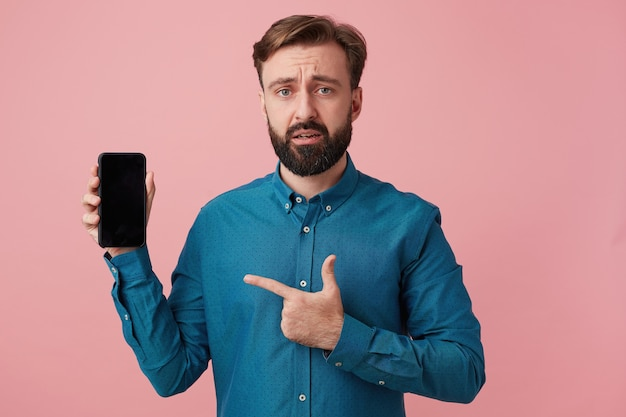 Frowning unhappy attractive bearded man, looking at camera, upset that his smartphone is outdated, wearing a denim shirt, pointing with finger to his device.