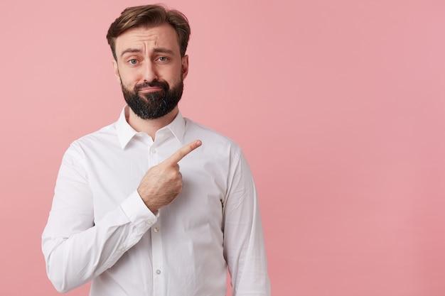 Accigliato uomo infelice vuole attirare la vostra attenzione puntando il dito sullo spazio della copia a destra, isolato su sfondo rosa.