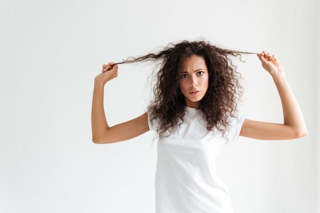 Donna insoddisfatta aggrottante le sopracciglia che tocca i suoi capelli e che esamina macchina fotografica