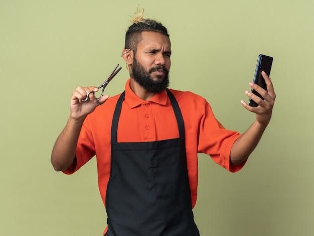 Accigliato giovane barbiere afroamericano che indossa un'uniforme con forbici e telefono cellulare guardando il telefono