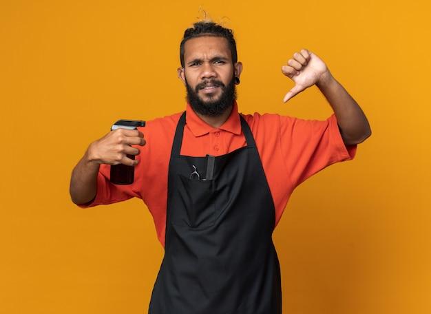 オレンジ色の壁に隔離された親指を下に示すヘアスプレーを保持している制服を着て眉をひそめている若いアフリカ系アメリカ人の男性床屋
