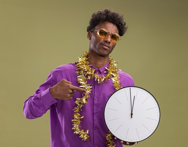 Хмурый молодой афро-американский мужчина в очках с гирляндой из мишуры на шее держит и указывает на часы, глядя в камеру, изолированную на оливково-зеленом фоне