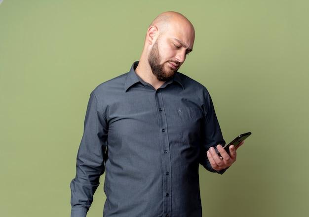 Accigliato giovane uomo calvo call center che tiene e guardando il telefono cellulare isolato su verde oliva