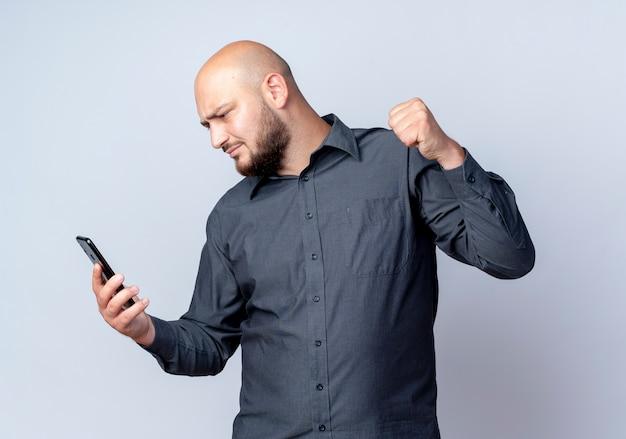 Accigliato giovane uomo calvo call center che tiene e guardando il telefono cellulare e alzando il pugno isolato su bianco