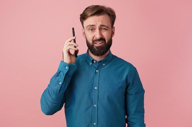 Accigliato giovane uomo barbuto, indossa una camicia di jeans, isolato su sfondo rosa. tiene il telefono lontano dall'orecchio, qualcuno urla nel telefono.