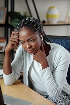 집에서 책상에 앉아 웹 세미나를 보거나 온라인 수업에 참석할 때 이어폰을 끼고 찡그린 젊은 흑인 여학생