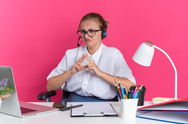ピンクの壁に隔離されたラップトップを見て手を一緒に保つ作業ツールで机に座っているヘッドセットと眼鏡を身に着けている眉をひそめている若いブロンドのコールセンターの女の子