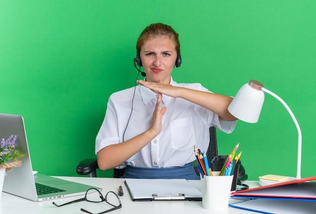 タイムアウトジェスチャーを行う作業ツールで机に座っているヘッドセットを身に着けている若い金髪のコールセンターの女の子をしかめっ面
