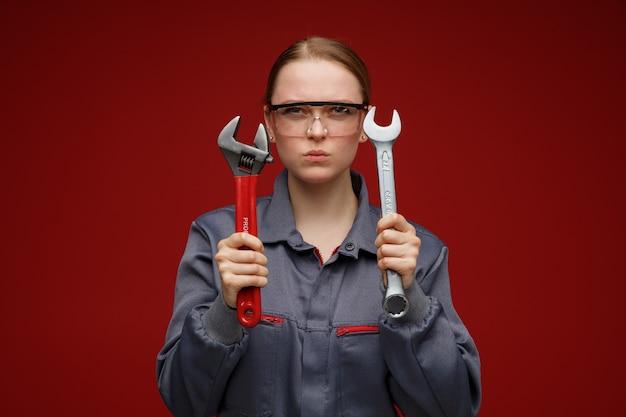 렌치를 들고 유니폼과 안전 안경을 쓰고 찡그림 젊은 금발 여성 엔지니어