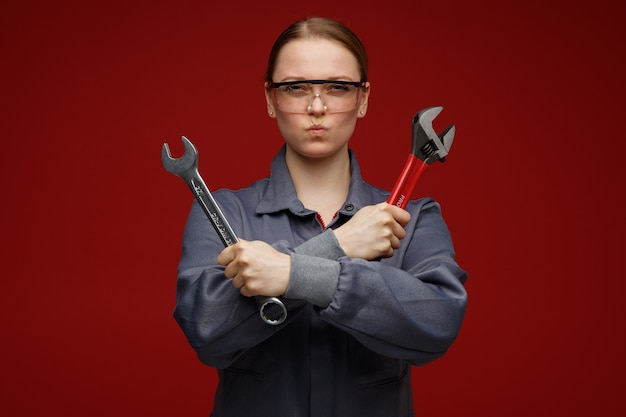 Frowning young blonde female engineer wearing uniform and safety glasses holding wrenches doing no gesture with pursed lips