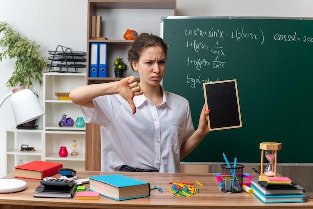 Accigliata giovane insegnante di matematica femminile bionda seduta alla scrivania con strumenti scolastici che tengono mini lavagna guardando la telecamera che mostra il pollice verso il basso in classe in