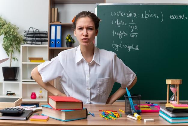 Accigliata giovane insegnante di matematica femminile bionda seduta alla scrivania con strumenti scolastici tenendo le mani sulla vita guardando la telecamera in classe